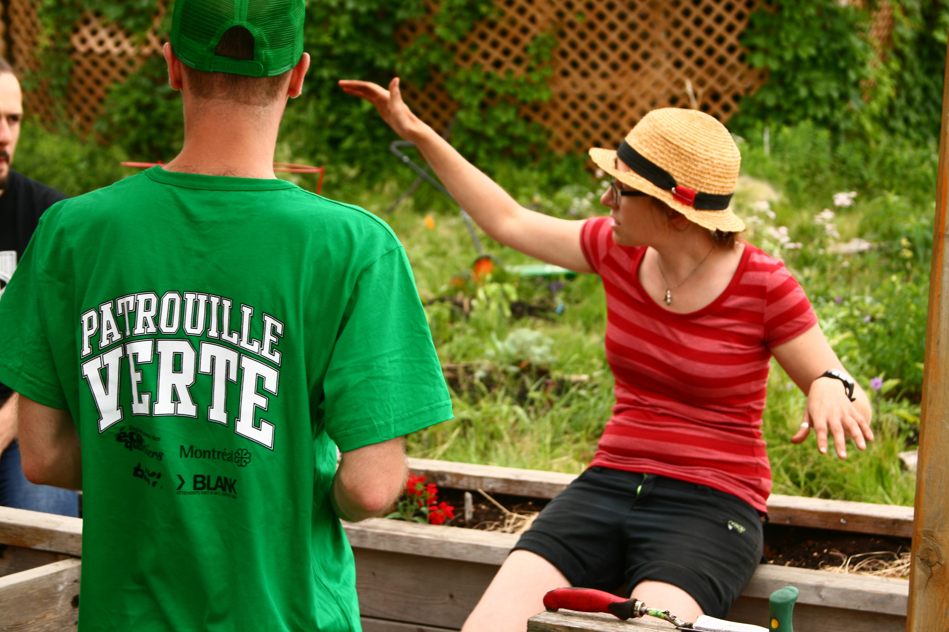 Une femme de face avec un chapeau et un homme de dos