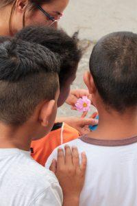 Des enfants de dos regardant une fleurs